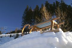 Sledge on snow. Low angle view of wooden sledge or toboggan on snow with trees in background Stock Image