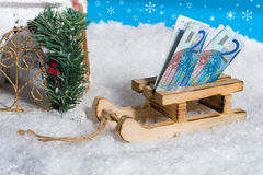 Sledge on snow with money gift. Blue sky with snowflakes stock photography