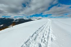 Sledge trace and footprints on winter mountain hill top Royalty Free Stock Image