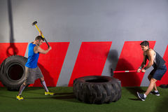 Sledgehammer Tire Hits men workout at gym. With hammer and tractor tire royalty free stock photos