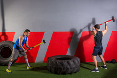 Sledgehammer Tire Hits men workout at gym. With hammer and tractor tire stock photo