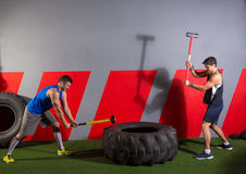 Sledgehammer Tire Hits men workout at gym. With hammer and tractor tire royalty free stock image