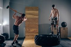 Sledgehammer Tire Hits men workout at gym with hammer and tractor tire. One men standing on tire royalty free stock photos