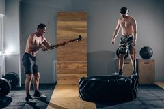 Sledgehammer Tire Hits men workout at gym with hammer and tractor tire. One men standing on tire stock photography
