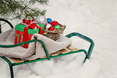 Sledges, blanket, basket with toys and gift boxes in a snowy for Royalty Free Stock Photos