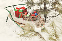 Sledges, blanket, basket with toys and gift boxes in a snowy for Stock Photo