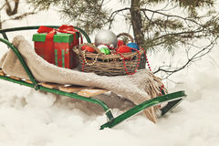 Sledges, blanket, basket with toys and gift boxes in a snowy for Royalty Free Stock Photo