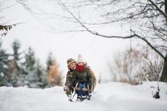 sledging在一个冬日的祖父和小女孩 免版税库存照片
