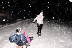 Sledging在晚上在冬天 库存图片