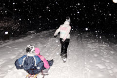 Sledging at night in winter. Girl pulling two children on a sled in the snow stock images