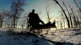sledging Un hombre con un movimiento de la mujer fuera de la nieve metrajes