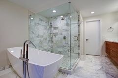 Sleek bathroom with freestanding bathtub and walk in shower. Sleek bathroom features freestanding bathtub paired with floor-mounted faucet atop marble floor Royalty Free Stock Images