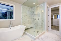 Sleek bathroom features freestanding bathtub. Atop marble floor placed in front of glass shower accented with rain shower head and gray and white marble stock photos