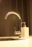 Sleek kitchen faucet.. Modern sleek kitchen faucet over  steel sink, surrounded by granite counter top Stock Photo