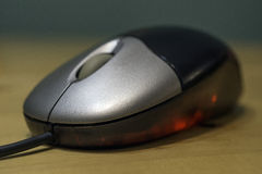 Sleek silver and black computer optical mouse with red light glo Stock Image