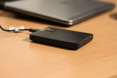 Sleek stylish external HDD connected to silver computer Royalty Free Stock Images