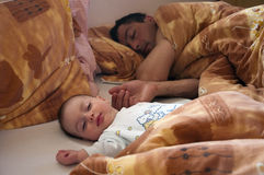 Sleep. Small baby and father sleeping in a bed, focus on a baby Stock Images