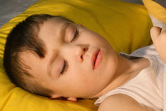 Sleep. Sick boy 3 years old is sleeping on a yellow pillow Stock Photos