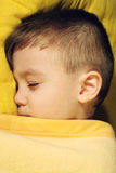 Sleep. Sick boy 3 years old is sleeping on a yellow pillow Royalty Free Stock Photo