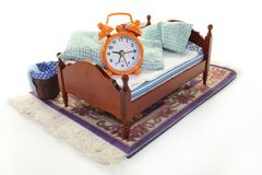 Sleep. A wooden bed and alarm clock on a white background Stock Image