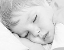 Sleep. Little boy sleep on white bed. High key Stock Photography