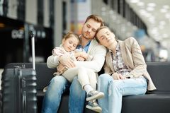 Sleep in airport. Two young parents and their little daughter napping in airport lounge while waiting for announcement of departure royalty free stock photo