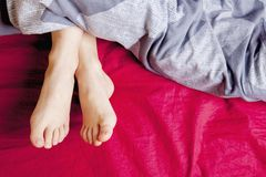 Sleep And Relax Concept. Top View On The Sleeping Girl Legs Under Blue Blanket Royalty Free Stock Image