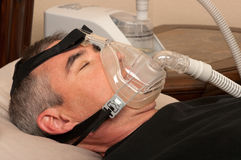 Sleep Apnea and CPAP. Man with sleeping apnea and CPAP machine royalty free stock photo