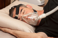 Sleep Apnea and CPAP. Man with sleeping apnea and CPAP machine stock photos