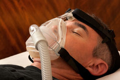 Sleep Apnea and CPAP. Man with sleeping apnea and CPAP machine stock images