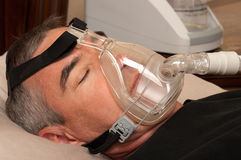 Sleep Apnea and CPAP. Man with sleeping apnea and CPAP machine royalty free stock images