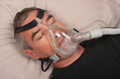 Sleep Apnea and CPAP. Man with sleep apnea and CPAP machine royalty free stock images