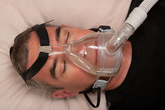 Sleep Apnea and CPAP. Man with sleep apnea and CPAP machine stock image