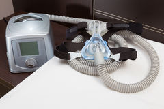 Sleep Apnea CPAP mask, hose, headgear, and machine. On bed, selective focus on CPAP mask stock photo