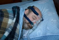 Sleep apnea device. Mature man (photographer is the model) sleeps on side using cpap nasal mask to treat sleep apnea stock image