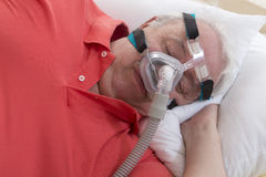 SLEEP APNEA SYNDROME SENIOR. Senior Man with sleeping apnea and CPAP machine stock images