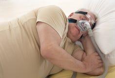 SLEEP APNEA SYNDROME SENIOR. Senior Man with sleeping apnea and CPAP machine Stock Photography