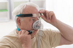 SLEEP APNEA SYNDROME SENIOR. Senior Man with sleeping apnea and CPAP machine royalty free stock photography