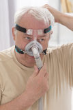 SLEEP APNEA SYNDROME SENIOR. Senior Man with sleeping apnea and CPAP machine stock image