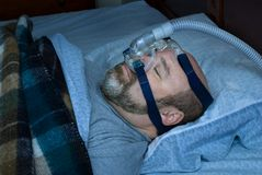 Sleep Apnea Treatment. Mature man (photographer is the model) sleeping on back with nasal mask and cpap device to treat sleep apnea. subdued lighting with blue Stock Photos