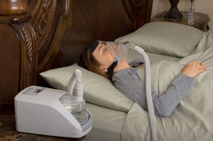 Sleep Apnea. Woman wearing CPAP machine for sleep apnea stock images
