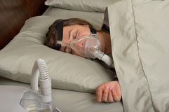 Sleep Apnea. Woman wearing CPAP machine for sleep apnea royalty free stock photography