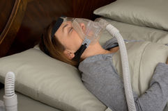 Sleep Apnea. Woman wearing CPAP machine for sleep apnea Royalty Free Stock Photos