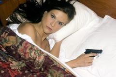 Sleep comes hard woman holds semi auto gun Royalty Free Stock Photo