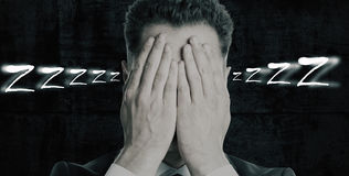Sleep concept. Portrait of man covering face with hands on dark background. Sleep concept Stock Photography