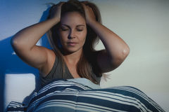 Sleep disorder, insomnia. young blond woman sitting on the bed a Royalty Free Stock Image