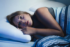 Sleep disorder, insomnia. young blonde woman lying on the bed aw Stock Photo