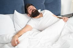 Sleep disorders concept. Man bearded hipster having problems with sleep. Guy lying in bed try to relax and fall asleep. Relaxation techniques. Violations of stock photos