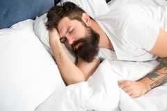 Sleep disorders concept. Man bearded hipster having problems with sleep. Guy lying in bed try to relax and fall asleep. Relaxation techniques. Violations of royalty free stock image
