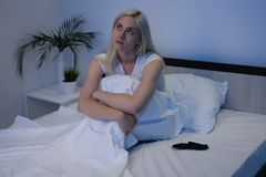 Sleep Disorders, insomnia. Woman Suffering From Depression Sitting On Bed In Pajamas. Image royalty free stock photo